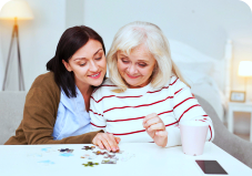 caregiver assisting senior woman in her activity
