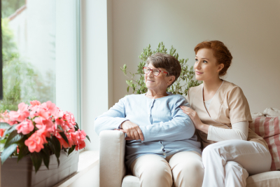 old woman and her caregiver looking outside