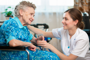 Nurse giving water to old woman
