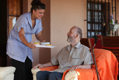 caregiver giving food to old man